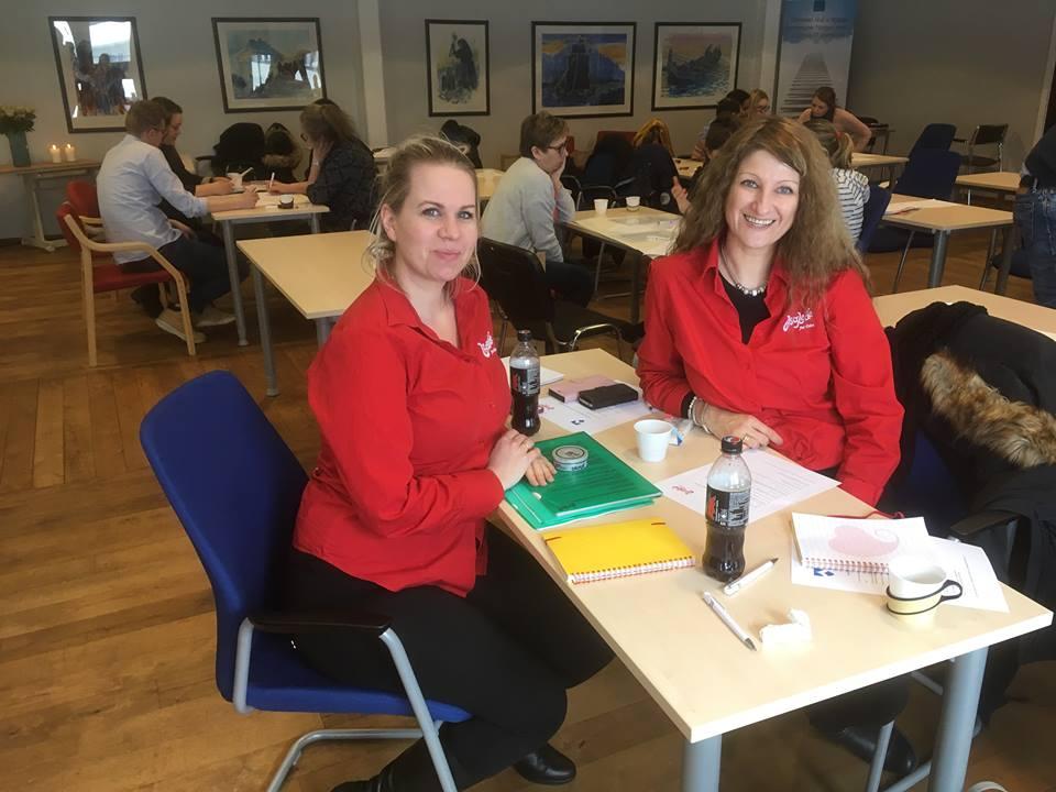 Sertifisører Christine Sandø Lundemo og Mia Solberg med livsgledegruppa i bakgrunnen, som ivrig jobber med gruppearbeidet.