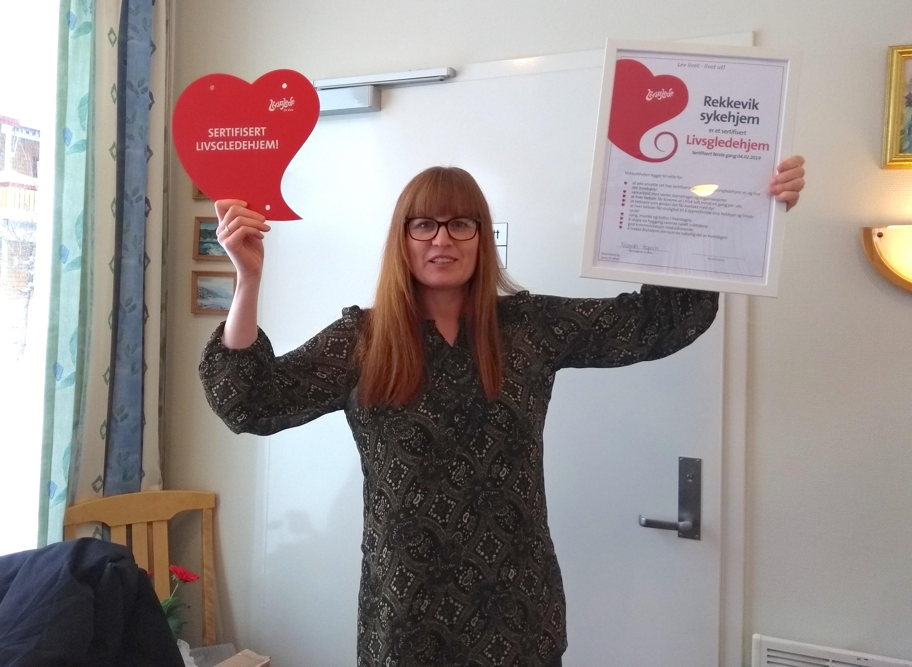 Avdelingsleder Henriette Schøyen Bredal holder sertifikat og plakett etter gjennomført sertifisering