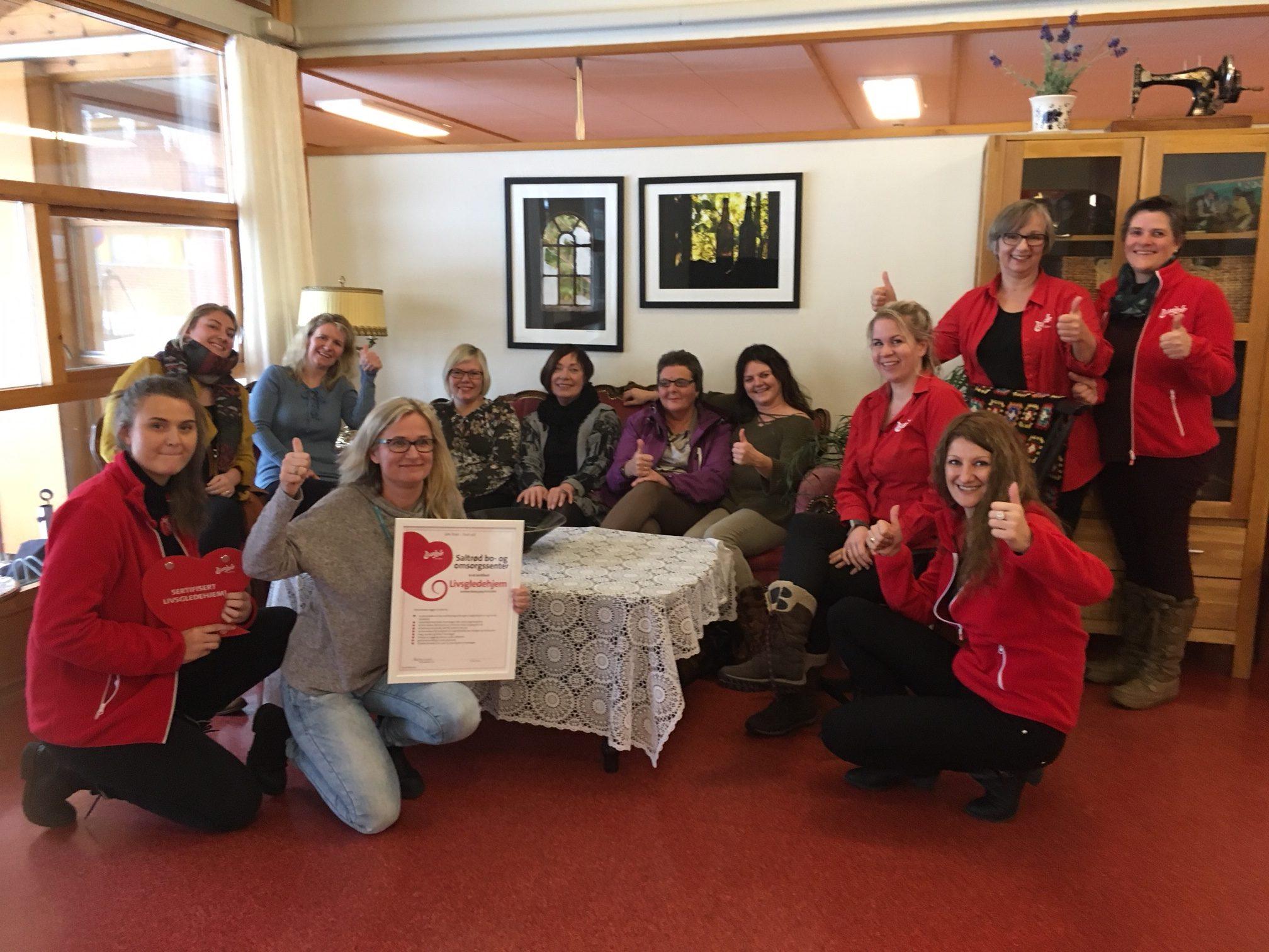 En glad og engasjert livsgledegruppe sammen med sertifisørene etter vellykket sertifisering som Livsgledehjem